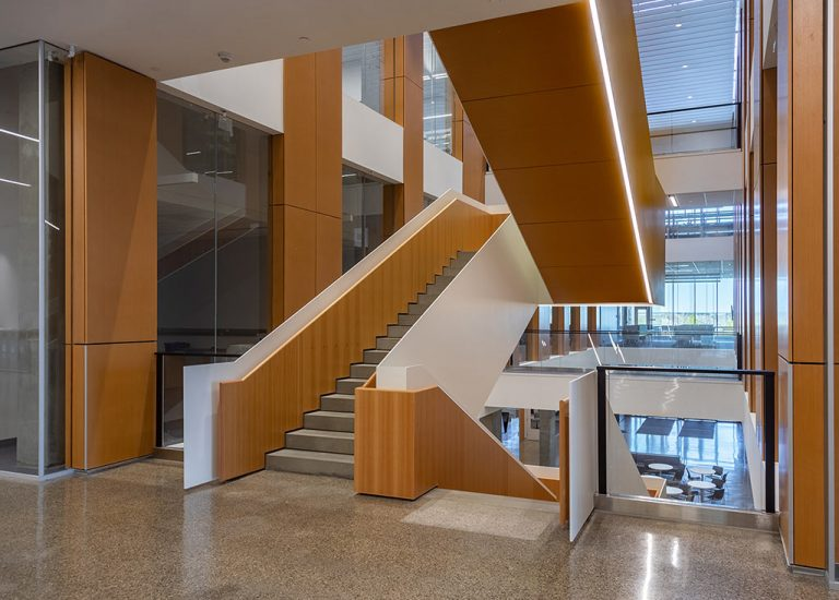 Acoustic Wood: Custom fabricated  perforated wood stair and column panels